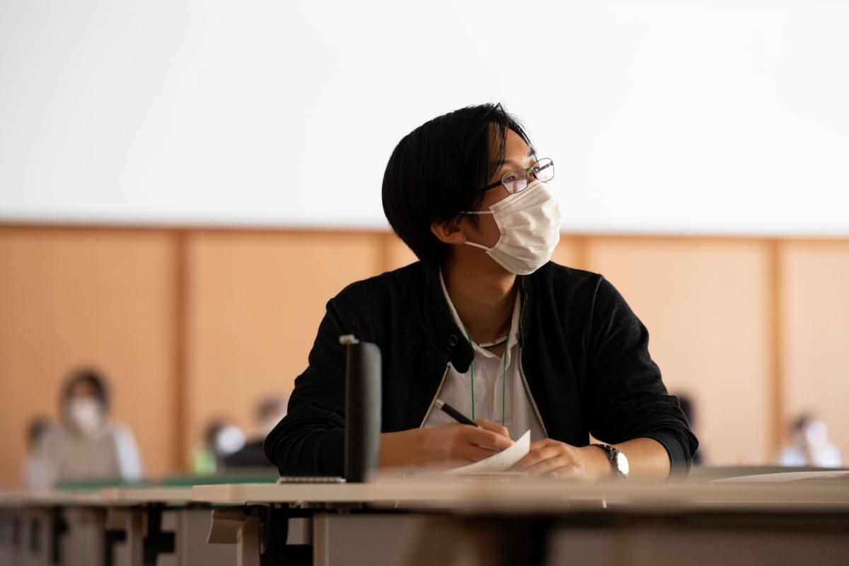 学校長の話を聴きながら、メモをとる本校生。
